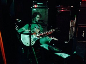 Our friend James Cameron Taylor guitarist for 'Ghost Police' playing with a broken leg at the 1011 bar .July 2014